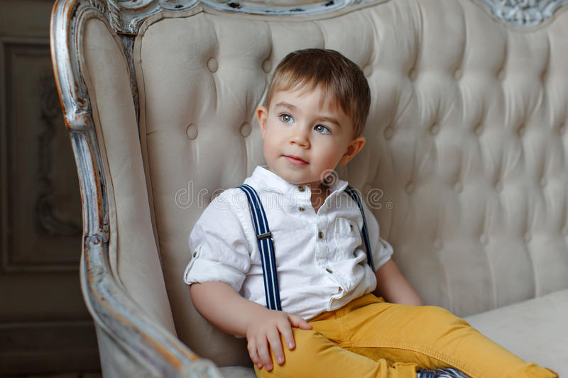 Small very cute boy in yellow pants and suspenders sitting in a stock image