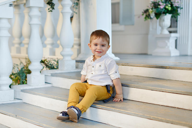 Small very cute, charming boy in yellow trousers sits on the sta stock photography
