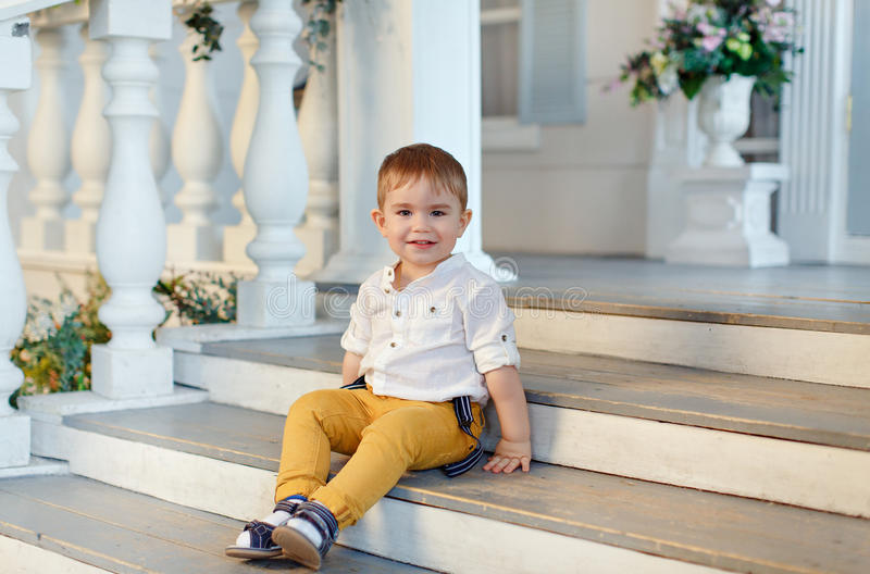 Small very cute, charming boy in yellow trousers sits on the sta stock images