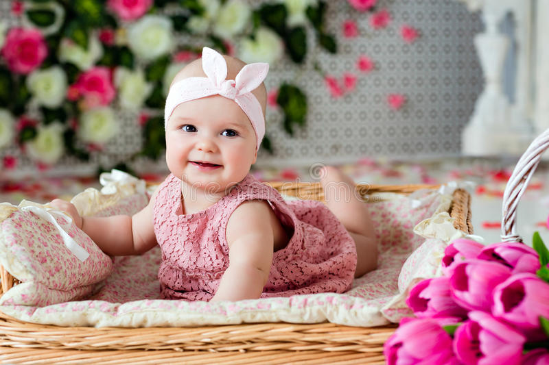 Small very cute wide-eyed smiling baby girl in a pink dress lying in a wicker basket about pink tulips royalty free stock photo