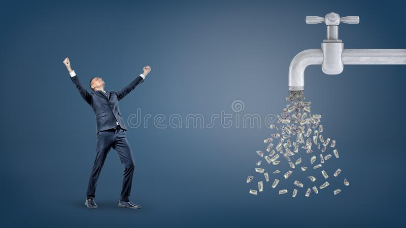 A small victorious businessman stands with raised arms near a giant water faucet leaking a lot of dollar bills. stock image