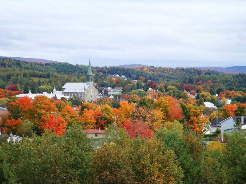 Small village church surrounded by bright autumn foliage in Quebec. The steeple of a small church stands out in a forest of bright color autumn leaves of maple stock photos