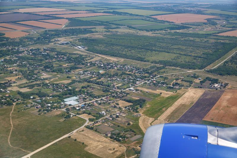 A small village, a green forest, yellow fields. View from the airplane royalty free stock image