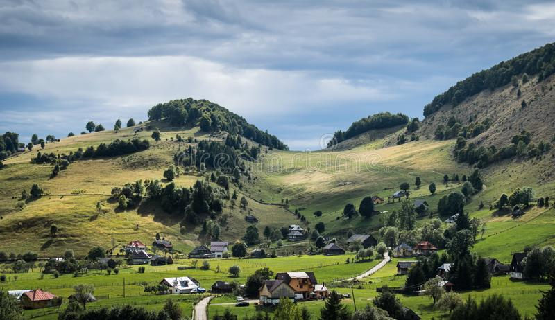 A small village in the mountains. A beautiful landscape with valleys, hills and mountains. The grass is still green in the early a stock photo