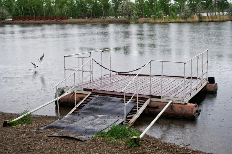 A small village pier on a lake or river for fishing and rowing boats during the summer rain stock photo