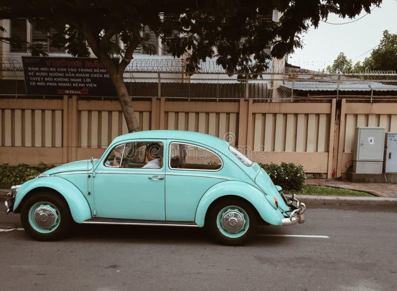 A small vintage blue car on street stock photos