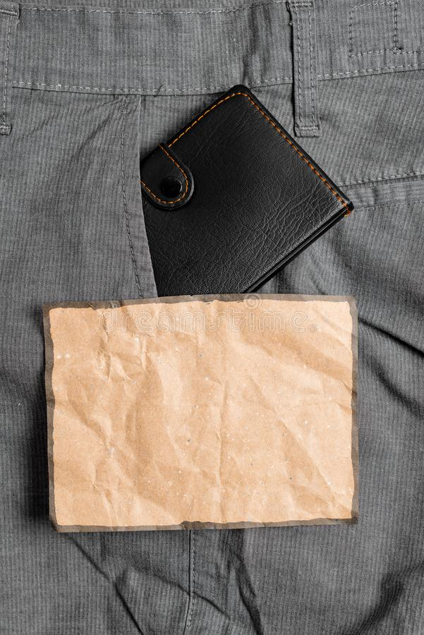 Small wallet in the trousers front pocket beside brown note sheet. Little purse is placed inside man pants near notation. Small little wallet inside man trousers stock photography