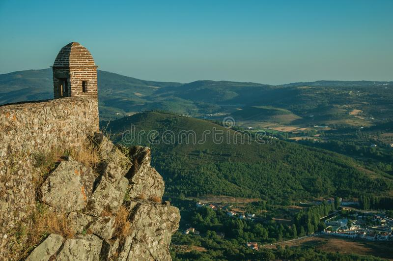 Small watchtower and stone wall over cliff with mountainous landscape stock photo