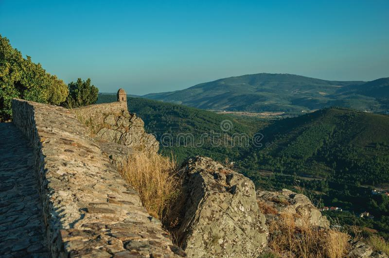 Small watchtower and stone wall over cliff with mountainous landscape royalty free stock images