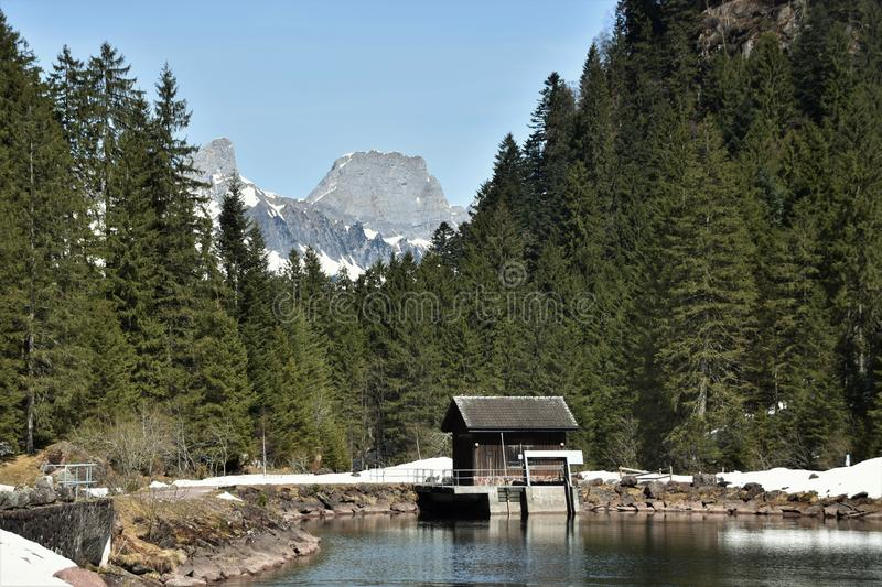 Small water dam surrounded by snow with wooden house near by tourist path heading directly towards to Murg lakes royalty free stock image