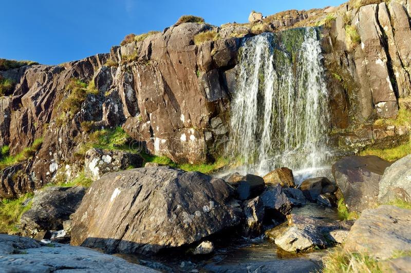 Small waterfall at the Conor Pass, one of the highest Irish mountain passes served by an asphalted road, located on the Dingle. Small waterfall at the Conor Pass stock image