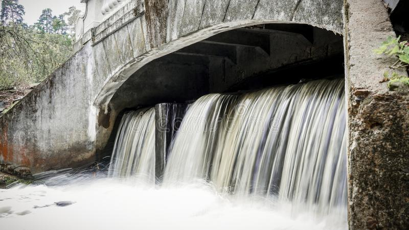 Small waterfall flowing from a samll dam. In the park stock image