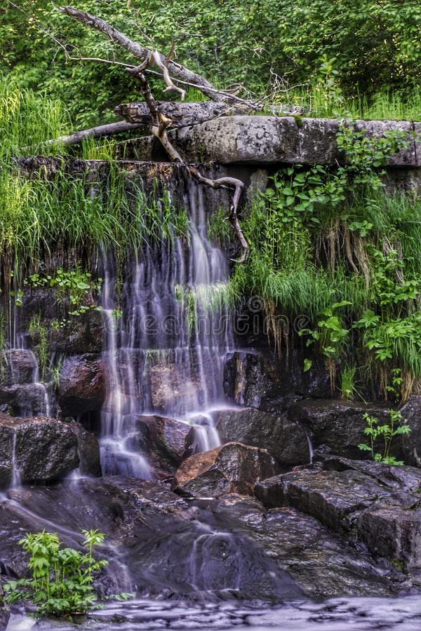 Small waterfall in old stone dam. River, stteam, summer, rocks, green, plant, forest stock photo