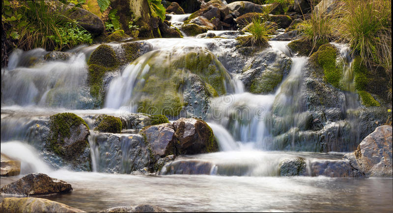 Small Waterfall in park with beautifull smooth water. Little waterfall in mountain forest with silky foaming water. royalty free stock images