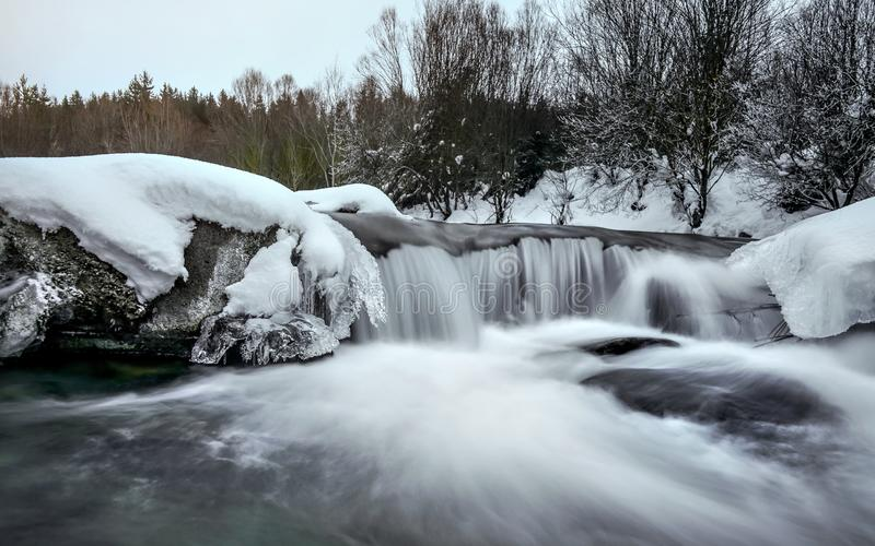 Small waterfall on river in winter, long exposure makes water milky smooth, snow and ice around, morning sun setting up distant stock photography