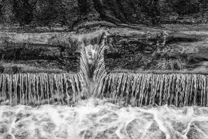 Small waterfall spillway in black and white stock image