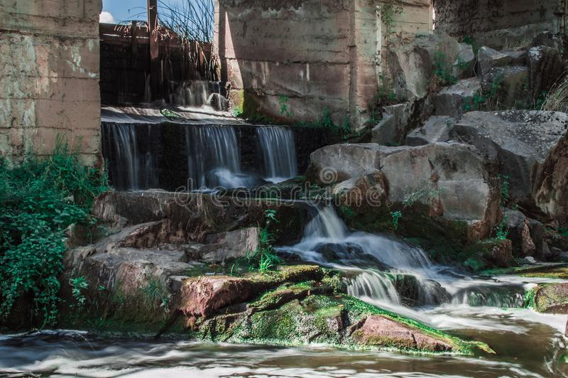 Small waterfall under the dam with rapids frome stones and green moss stock photography