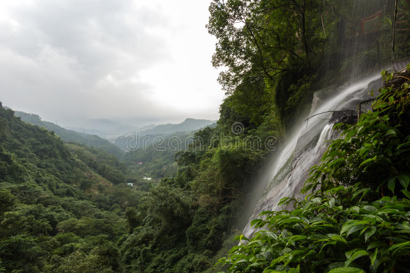 Small waterfall and view over lush forest in Taipei. Small waterfall and view over lush, verdant and hilly forest in Taipei, Taiwan royalty free stock images