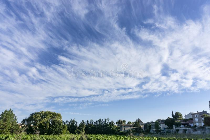 Small wave of beautiful white fluffy clouds on vivid blue sky in a summer time above houses and green trees in Vacqueyras village stock images