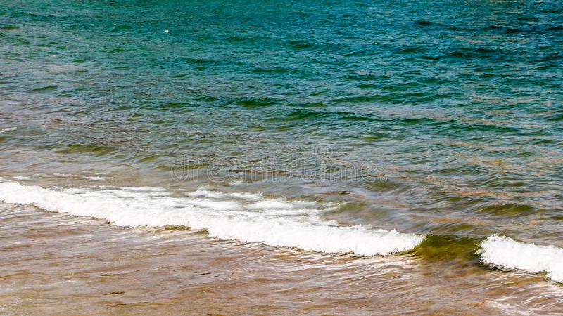 A small wave breaking on the sand of the shore royalty free stock image