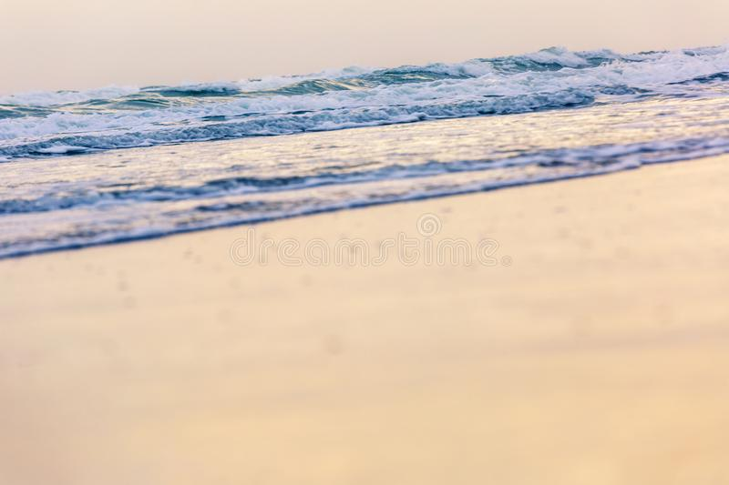 Small wave coming to the beach and glassy fluffy white breaking wave on the sand with gold sunlight for background stock photo