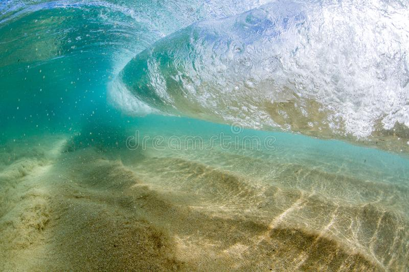 Under water view of Small wave breaking over sandy beach at waimea bay hawaii. Small wave crashing on the beach at waimea bay hawaii underwater royalty free stock image