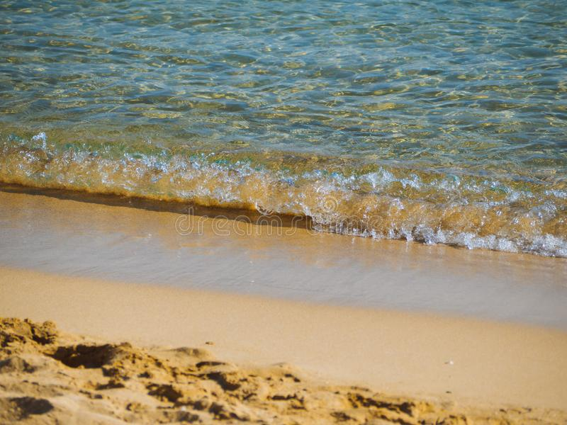 Small waves on a nice empty sandy beach - crystal clear water stock photo