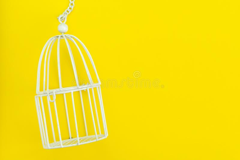 Small white bird cage on solid yellow background using as protection, limit freedom or liberty concept.  stock images