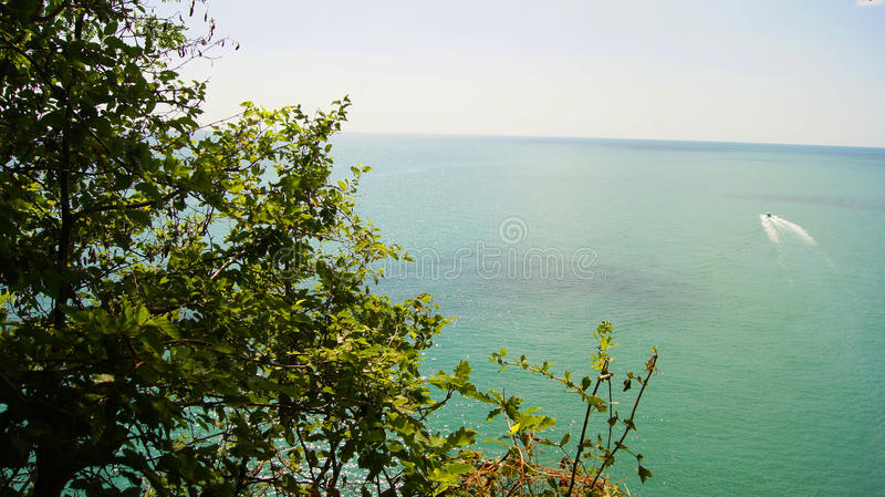 Small white boat sailing from the coast of the azure sea waters to the horizon. Small white boat sailing from the coast to the blue sea in the daytime under the stock photos