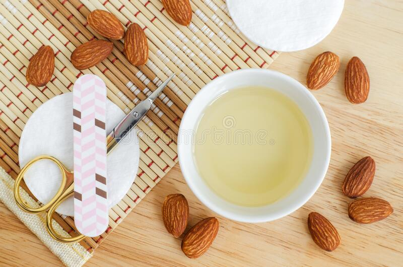 Small white bowl with almond oil, scissors and nail file for natural nails and cuticle treatment. Manicure and pedicure concept. Top view, copy space royalty free stock images