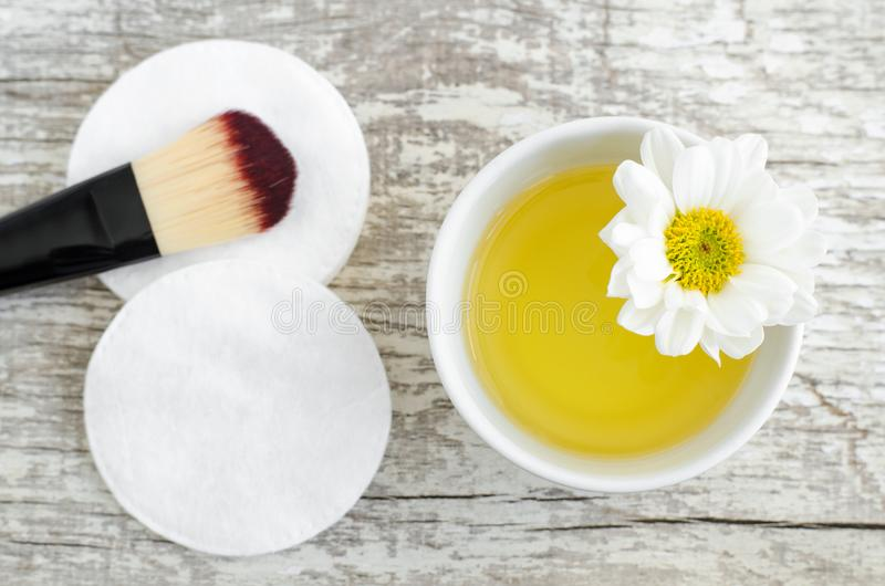 Small white bowl with cosmetic/cleansing oil and cotton pad for natural skin care. Homemade cosmetics. stock image