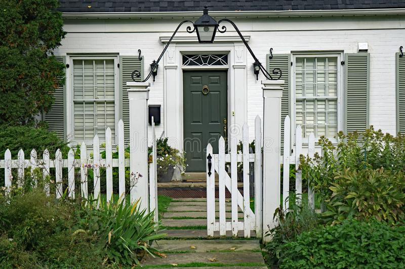 Small white brick house. Front door of small white brick house with picket fence stock photo