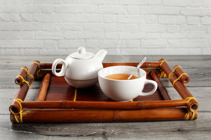 Small white ceramic teapot and cup of hot steaming black tea wit royalty free stock images