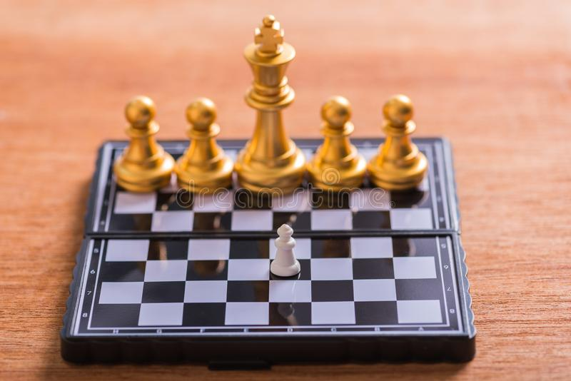 A small white chess pieces against very big gold chess team on b royalty free stock photos
