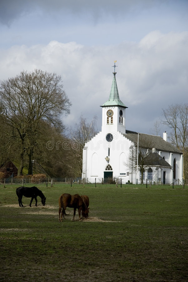 Small white church. In a landscape with horses stock photos