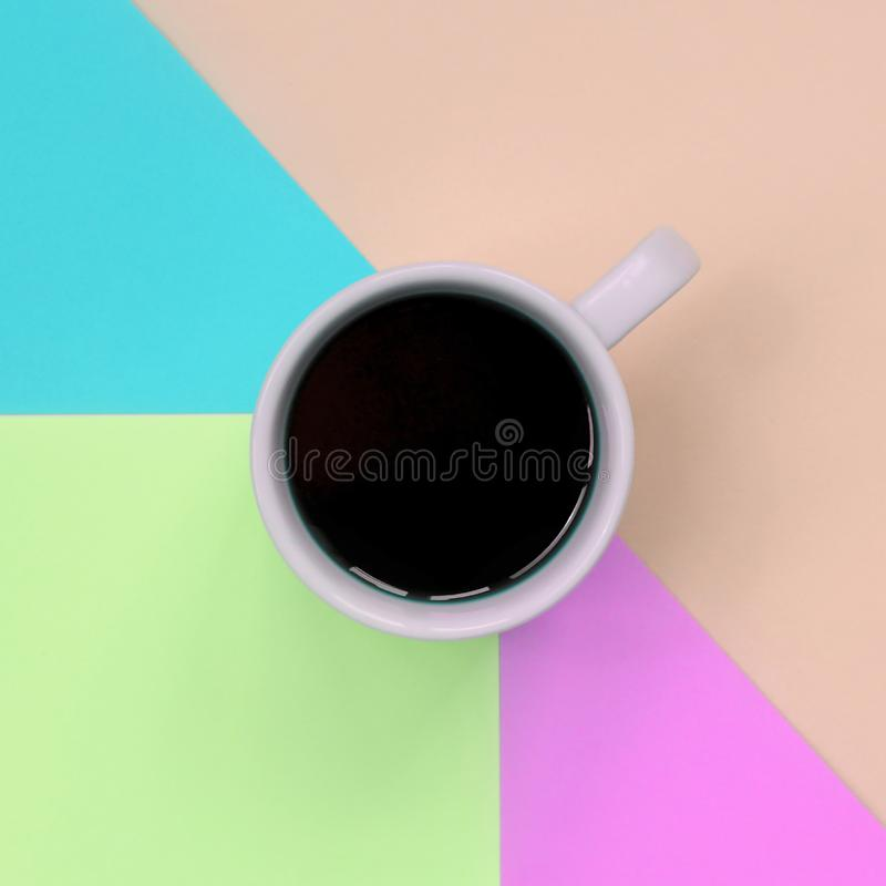 Small white coffee cup on texture background of fashion pastel pink, blue, coral and lime colors paper royalty free stock photography