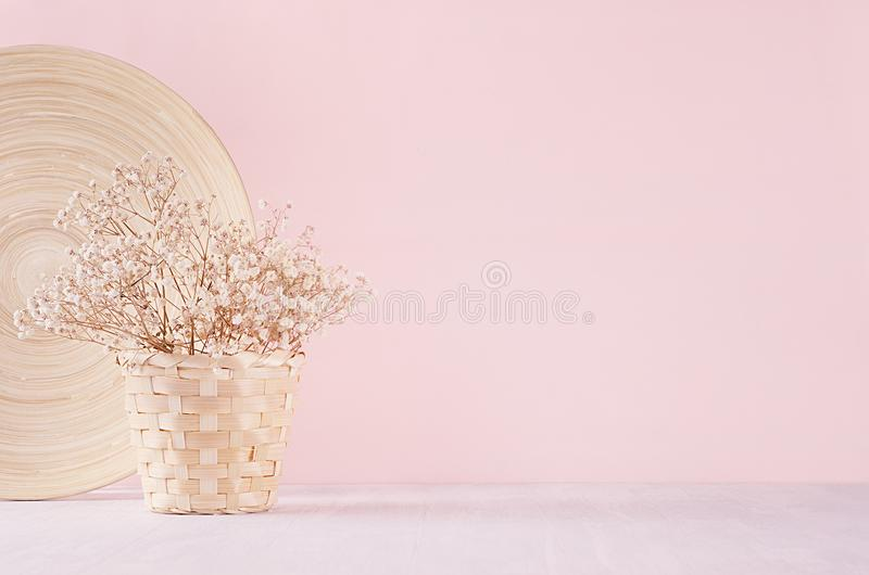 Small white dried flowers in beige wicker basket and bamboo plate on soft pink pastel background. royalty free stock photo