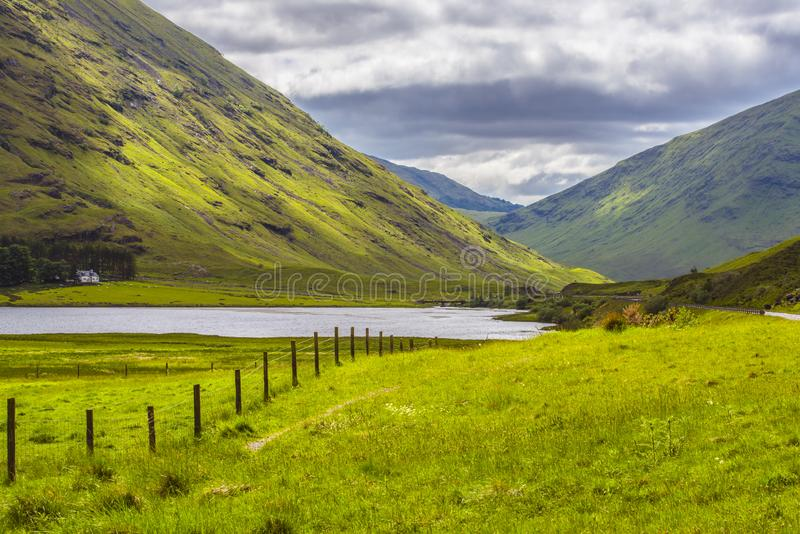 At Home In The Mountains. A small white farmhouse sits snugly under ancient mountains in the Highlands of Scotland stock photo