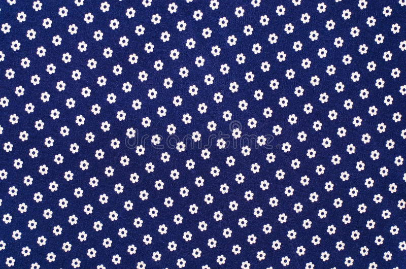 Small white floral pattern on dark blue fabric. stock image