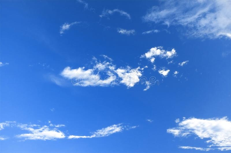 Small white fluffy clouds. Bright blue sky with small white fluffy clouds royalty free stock photo
