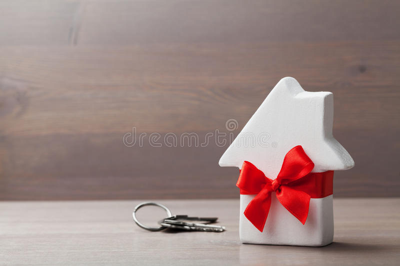 Small white house decorated red bow ribbon with bunch of keys on wooden background. Gift, real estate or buying a new home stock photos