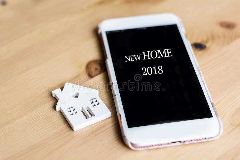 Small White House Model and Smart Phone.New Home for 2018 Concept. Small White House Model and Smart Phone On Wooden Background royalty free stock image