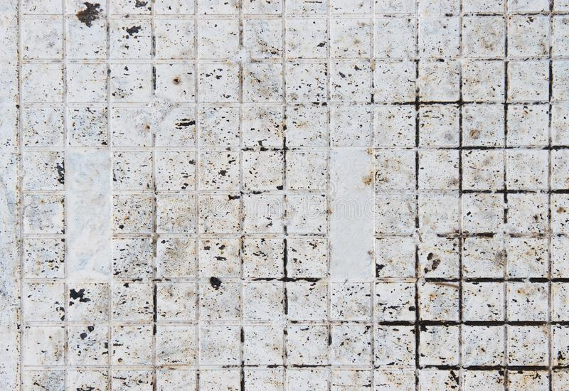 Small white metal square tiles covered with dirt. White background made out of small tiles stock image