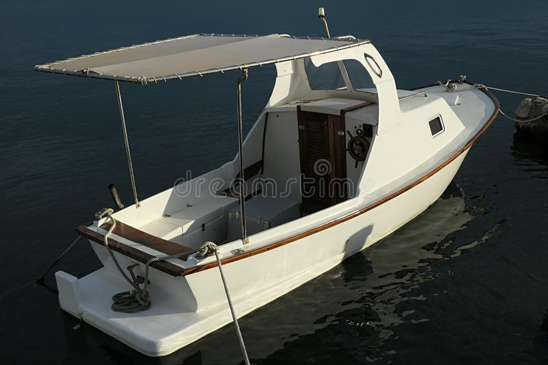 Small white motor fishing boat with wooden helm, simple small cabin in front royalty free stock photography