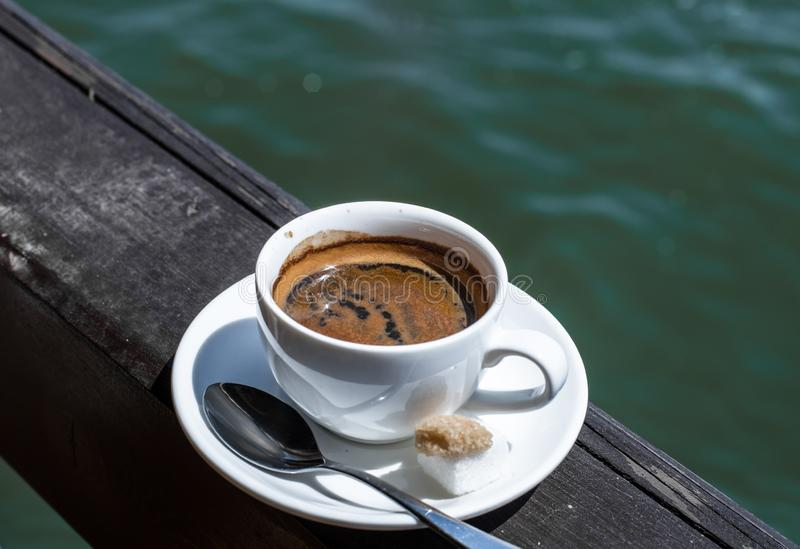 A small white porcelain espresso cup on a saucer with a teaspoon and two pieces of sugar stock images