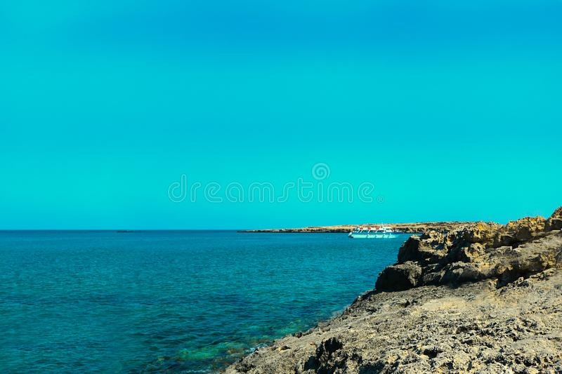Small white ship far away at harbor. Aerial view of boat at daytime. Landscape with boat, rocks, sea, blue sky. Floating boat in. Small white ship far away at stock image
