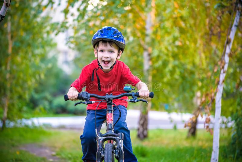 A small white Toddler boy in a protective helmet on his head sits on a children`s bicycle. Toddler on a two-wheeled red bicycle royalty free stock photo