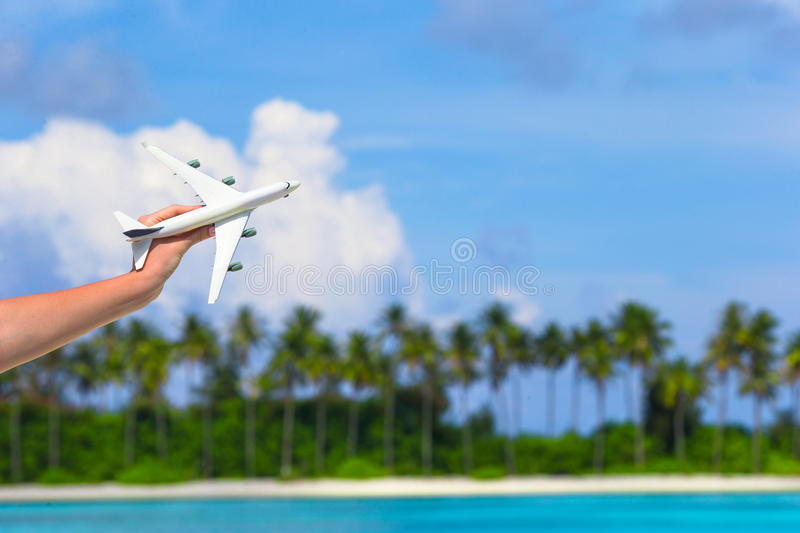 Small white toy airplane on tropical beach in stock photography
