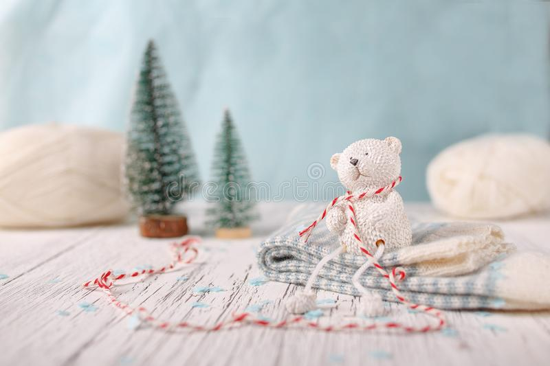 A small white toy bear is sitting on a pile of socks. A white wooden background on which there are two Christmas trees and a skein of yarn. Good New Year stock photos