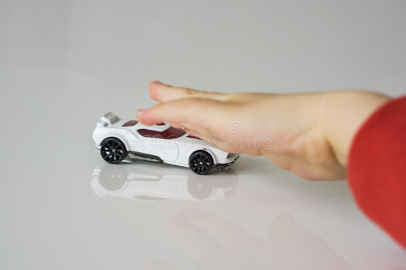 Small white toy car, pushed by children`s hand. The hand is defo. Small white toy car, pushed by children`s hand, the hand is defocuses stock image